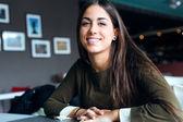 Beautiful girl drinking coffee sitting indoor in urban cafe. — Stock Photo