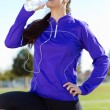 Pretty young woman drinking water after running. — Stock Photo #58269939