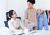 Two young businesswomen working with digital tablet in her offic — Stock Photo