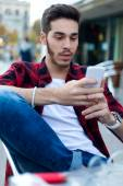 Young entrepreneur using his mobile phone at coffee shop.  — Stockfoto