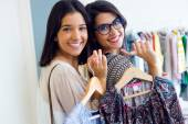 Two beautiful girls shopping in a clothes shop. — Stockfoto