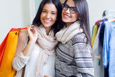 Two beautiful girls shopping in a clothes shop. — Foto Stock