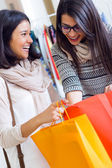 Two beautiful girls shopping in a clothes shop. — Stock Photo
