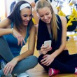Young women using mobile phone in the gym. — Stock Photo #60947971
