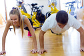 Young people doing exercise on the floor in the gym. — Foto de Stock