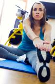 Young woman stretching her leg to warm up in the gym. — Stock Photo