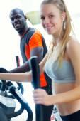 Gente joven con la máquina elíptica en el gimnasio. — Foto de Stock