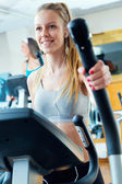 Young people with elliptic machine in the gym. — Stock Photo