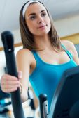 Young woman with elliptic machine in the gym. — Stock Photo