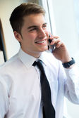 Young businessman using his mobile phone in office. — Stockfoto