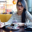 Young beautiful woman using her mobile phone in coffee. — Stock Photo #64774233