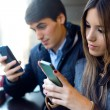 Young couple using mobile phone in cafe. — Stock Photo #65722971