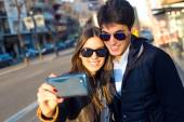 Happy young couple taking selfies with smartphone. — Stock Photo