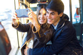 Young couple taking selfies with smartphone at bus. — Foto Stock