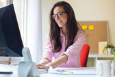 Beautiful young woman working in her office. — Stock Photo