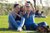 Group of students taking photos with a smartphone in the street. — Stock Photo