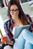 Beautiful young woman using her digital tablet at home. — Stock Photo