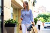 Beautiful young woman walking in the street. Shopping concept. — Stock Photo