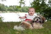 Happy baby and puppy near the lake — Stock Photo