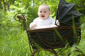 Happy baby in vintage pram — Stock Photo