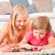Kids Using Tablet Lying On Carpet — Zdjęcie stockowe #53302431