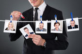 Businessman Selecting Candidate From Clothesline — Stock Photo