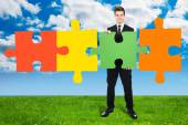 Confident Businessman Solving Jigsaw Puzzle On Field — Stock Photo