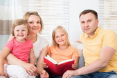 Family Reading Book At Sofa — Stock Photo