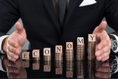 Businessman Protecting Economy Blocks On Stacked Coins — Stock Photo
