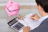 Man calculating savings and costs — Stock Photo