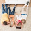 Kids Using Tablets Lying On Carpet — Stock Photo #55360145