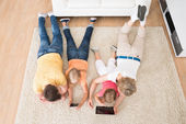 Kids Using Tablets Lying On Carpet — Stockfoto