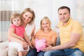 Family Saving Money In Piggybank — Stockfoto