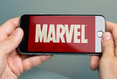 Hands Holding Apple iPhone 6 With Logo Of Brand Marvel — Stock Photo