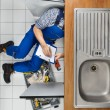 Plumber Examining Kitchen Sink — Stock Photo #62702111