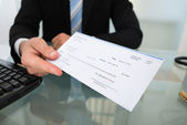 Midsection Of Businessman Giving Cheque — Stock Photo