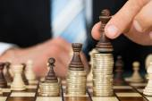 Businessman Placing Chess Pieces On Coins — Stock Photo