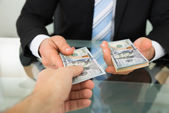 Businessman Passing Money To Colleague — Stock Photo