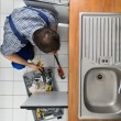 Plumber Examining Kitchen Sink — Stock Photo #63324401