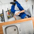 Plumber Examining Kitchen Sink — Stock Photo #63324405