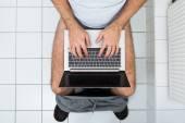 Man In Toilet Using Laptop — Stock Photo