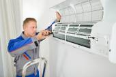 Electrician Repairing Air Conditioner — Stock Photo