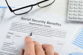 Hand Over Social Security Benefits Form — Stock Photo