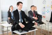 Meditating Businesspeople Sitting On Desks — Stock Photo