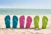 Pairs Of Flip-flops On Beach — Stock Photo