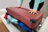 Woman Trying To Close Suitcase — Stock Photo