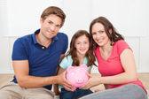 Family Holding Piggy Bank — Stock Photo