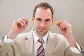 Businessman With Yellow Earplugs — Stockfoto