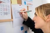 Businesswoman Writing On Weekly Time Sheet — Stockfoto