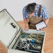Electrician Looking At Fuse Box — Stock Photo #74131537